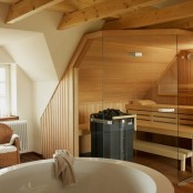 a tiny steam room clad with wood, with wooden benches and built-in lights plus glass walls