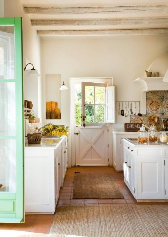 a white cottage kitchen with rustic cabinets, whitewashed wooden beams on the ceiling, a colorful mosaic tile backsplash and jute rugs