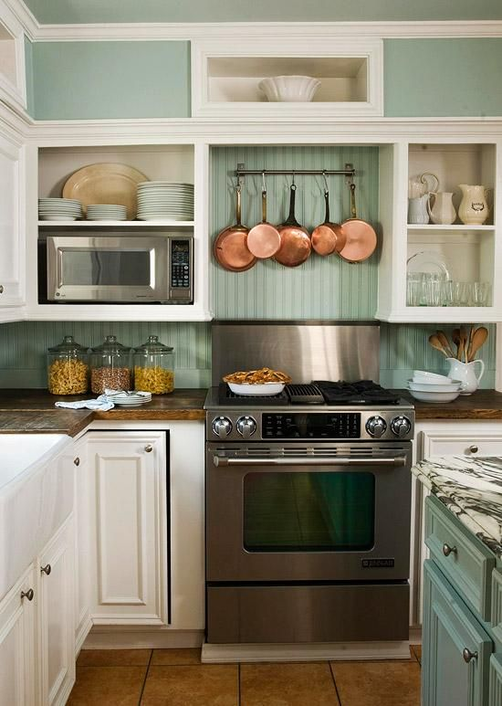 a cozy mint-colored and white cottage kitchen with open and closed storage units, a metal cooker and copper pans for decor is a very stylish space