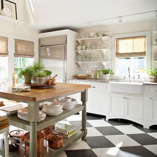 a cottage kitchen with vintage white cabinets, a subway tile backsplash, a grey table kitchen island and woven shades plus a checked floor
