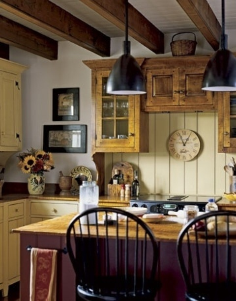 a neutral cottage kitchen with a yellow beadboard backsplash and yellow cabinets, a purple kitchen island, wooden beams and black pendant lamps
