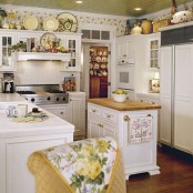 a lovely cottage kitchen with a yellow ceiling, white cabinets and a compact kitchen island, a floral wallpaper accent, decorative porcelain and floral textiles