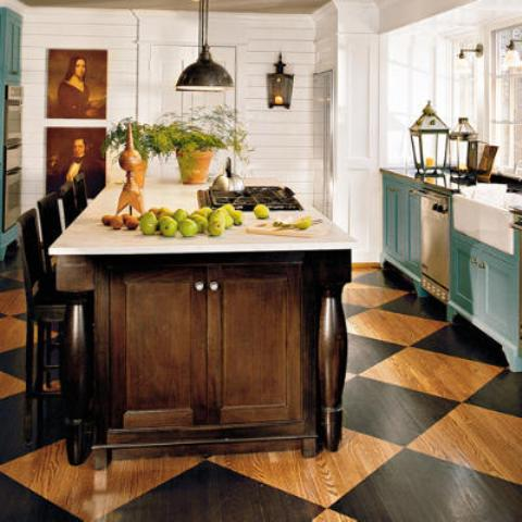 an English cottage kitchen with a checked floor, blue cabinets, a dark stained kitchen island and pretty artworks and vintage lamps