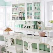 an airy and welcoming cottage kitchen with light green and white cabinets, tableware and cookware in greens, pendant lamps and vintage stools