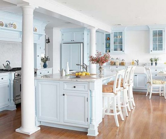 an airy light blue cottage kitchen with vintage cabinets, white vintage stools and pillars for a refined touch in the space