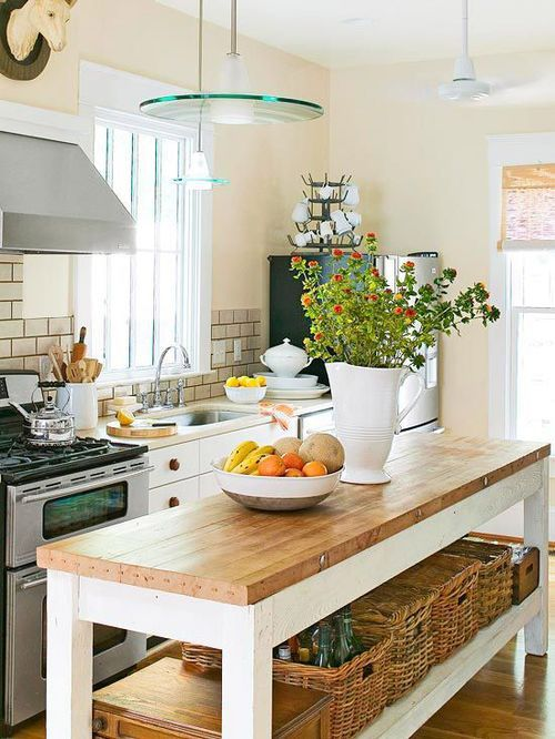 a charming cottage kitchen with a long table kitchen island, white cabinets with wooden knobs, pendant lamps and baskets plus bold blooms