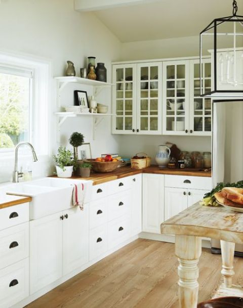 a neutral cottage kitchen with white cabinets and stained butcherblock countertops, a shabby chic table kitchen island and a vintage pendant lamp
