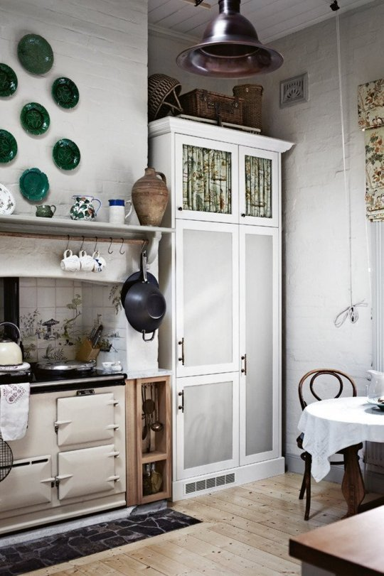 a neutral cottage kitchen with a vintage hearth, a grey and white storage unit, green decorative plates, a pendant lamp and stained furniture