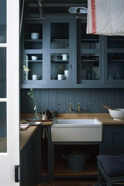 a modern cottage kitchen with graphite grey cabinets and a backsplash, butcherblock countertops and a built-in sink plus white porcelain