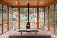 super cozy sunroom filled with natural wood and a wood-burning stove