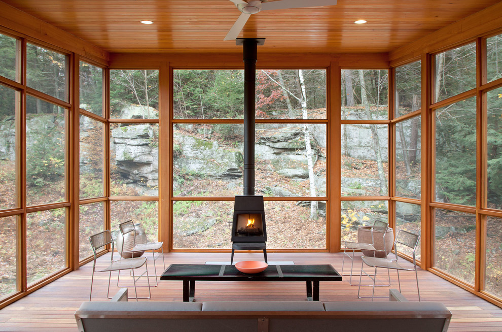 super cozy sunroom filled with natural wood and a wood burning stove