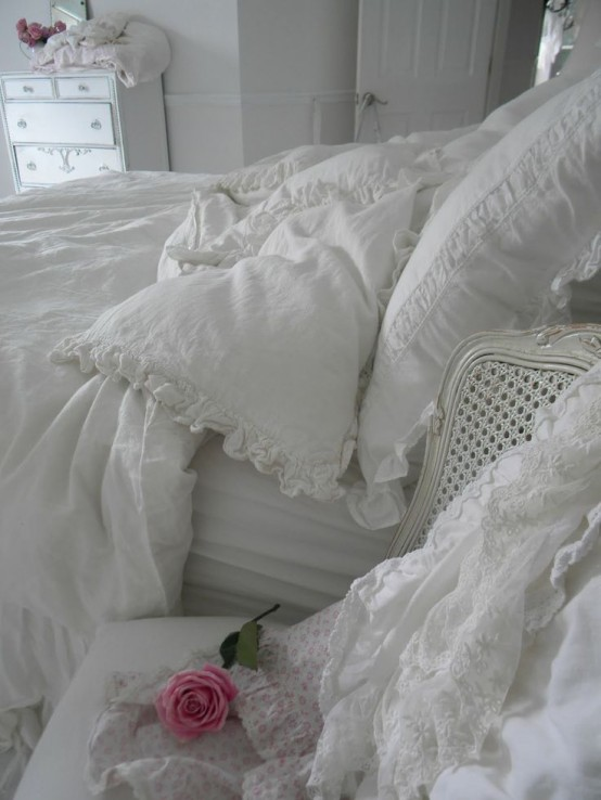 a white shabby chic bedroom with refined furniture, white lace and ruffle bedding and floral touches