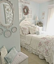 a pastel blue shabby chic bedroom with refined white furniture, floral bedding, decorative plates and shutters and potted blooms