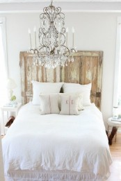 a neutral shabby chic bedroom with a shabby wooden screen, a crystal chandelier, refined vintage furniture