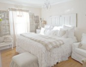 a white shabby chic bedroom with shabby shutters on the walls, sophisticated neutral furniture, white ruffle bedding and chic details