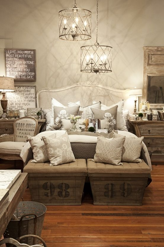 a vintage rustic bedroom with wooden furniture, pendant lamps, lots of artworks and printed chests at the foot of the bed