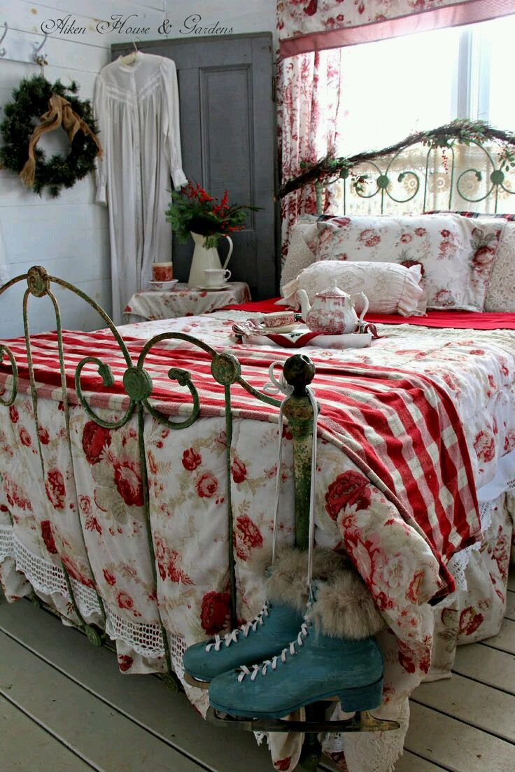 a vintage bedroom decorated for Christmas, with a forged bed, a blue door, greenery, fir and red and white plaid touches