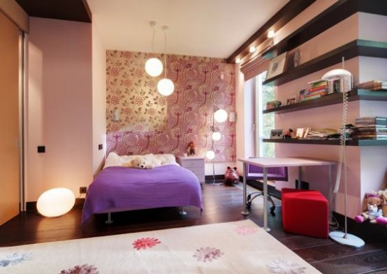 a bright teen bedroom with a printed wall, dark wall shelves, a lilac bed and a bright red ottoman and a printed rug