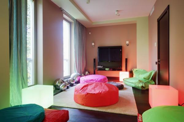 a super bright contemporary space with colorful cushions and pillows plus ottomans and bright curtains to spend time with friends
