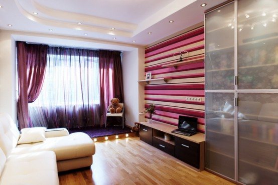 a colorful contemporary teen bedroom with purple curtains, a striped accent wall, an elegant white sofa, a sheer wardrobe with sliding doors
