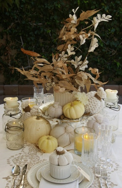 a delicate white rustic Thanksgiving tablescape with white linens, porcelain, pumpkins, a white knit coverup for the vase is elegant