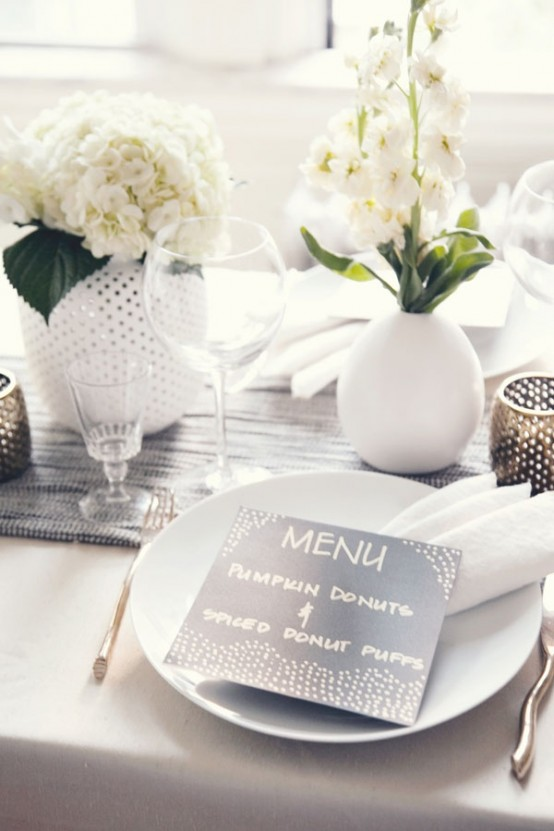 a modern white Thanksgiving tablescape with a grey runner, a black card and a dark perforated candleholder is very chic