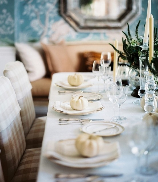 a chic and refined white Thanksgiving tablescape with white linens, porcelain, pumpkins and candles and greenery in bowls is chic