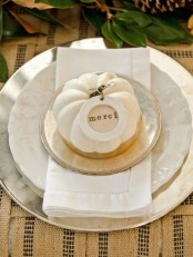 white and mother of pearl porcelain with a gold edge, a white pumpkin and a card for a chic place setting at Thanksgiving