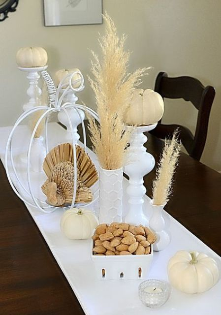white linens, white pumpkins, pampas grass and candlesholders shaped as pumpkins for a chic rustic Thanksgiving tablescape