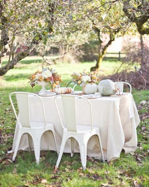 white linens, white chairs, pastel and whitewashed pumpkins, white blooms and greenery for a chic Thanksgiving look