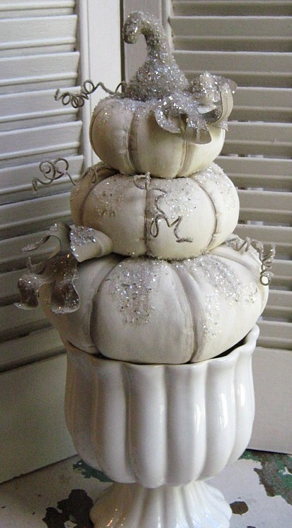 a porcelain bowl with white pumpkins stacked, twigs and glitter makes up a chic and beautiful Thanksgiving decoration in vintage style