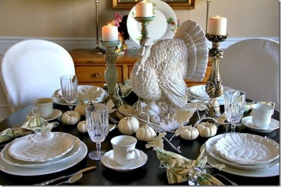 white porcelain, white pumpkins, candles and a large turkey paired with a dark table give a bold and contrasting look to the table
