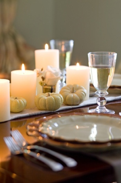white linens, mini pumpkins, candles and white roses plus white porcelain with a gold edge give a refined yet rustic look to the table