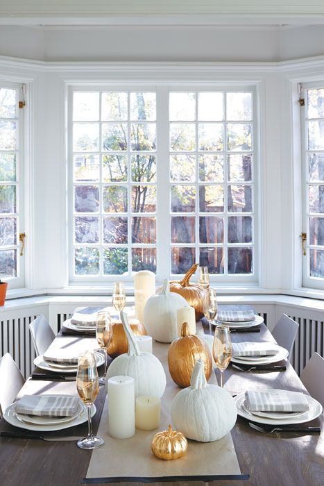 a modern Thanksgiving tablescape with white porcelain, pumpkins and candles, a woven charger and striped napkins is beautiful