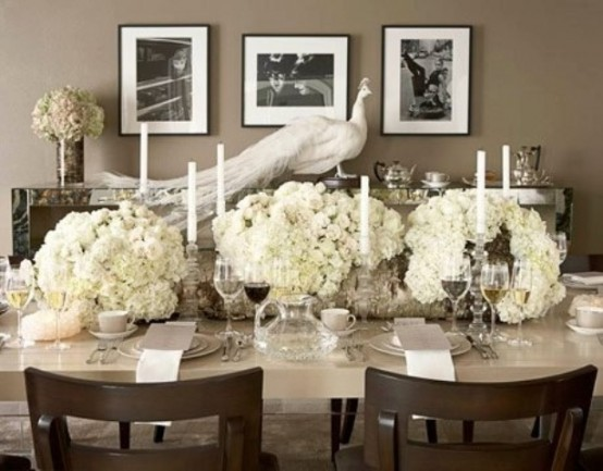 a refined neutral and white Thanksgiving table with white candles, blooms napkins, grey cards and mugs is very refined