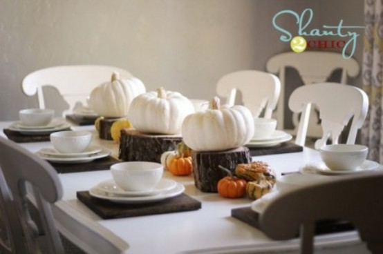 a modern rustic Thanksgiving table with brown placemats, white porcelain, white pumpkins on tree stumps