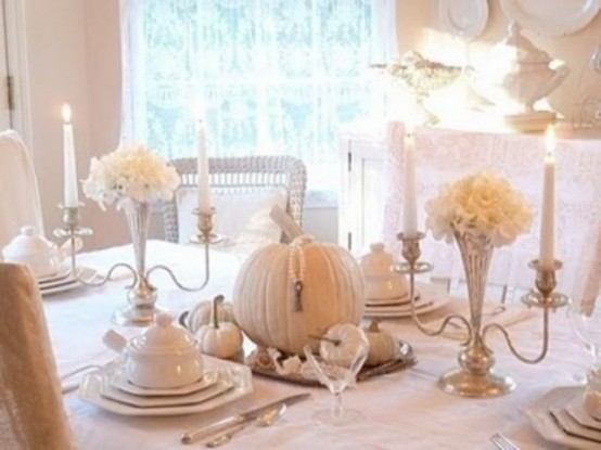 a vintage white Thanksgiving tablescape with white porcelain, pumpkins, blooms in silver candleholders is chic and bold