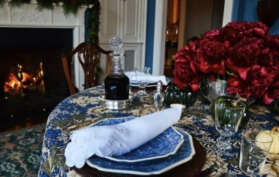 a patterned blue tablecloth and blue porcelain plus red blooms and gold touches for a chic and elegant tablescape