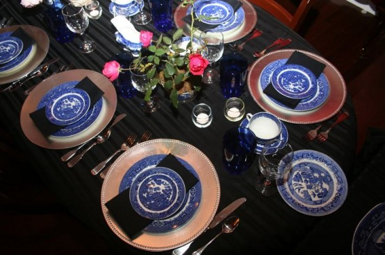 blue and white porcelain and bold blue glasses paired with metallic touches and bold blooms make up a bold Thanksgiving tablescape