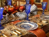 a traditional Thanksgiving tablescape in orange and blue, with burlap, hay, pumpkins and blue glasses