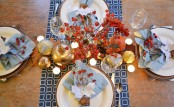powder blue napkins and a bold blue and white printed table runner paired with gold veggies and bold dried blooms and berries look cool