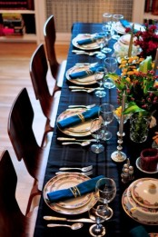 a blue plaid tablecloth and bold blue napkins paired with fall-colored arrangements and gold candles make the tablescape amazing