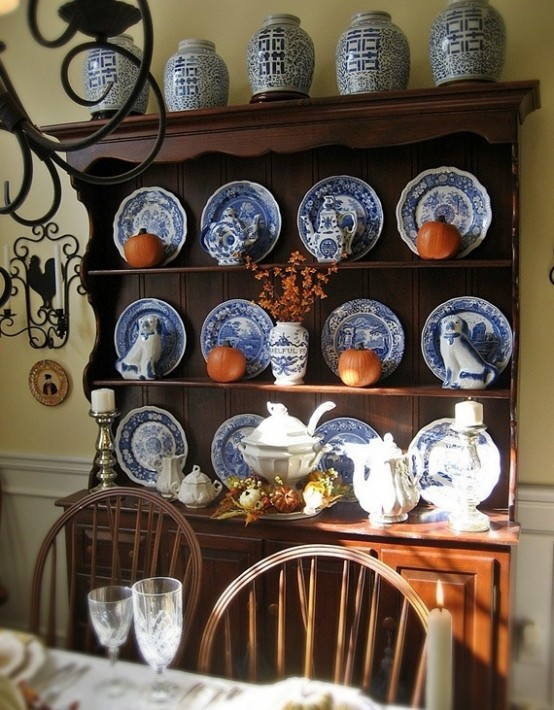 a chic Thanksgiving display with blue and white plates and orange pumpkins for a contrast is a very cool idea to try