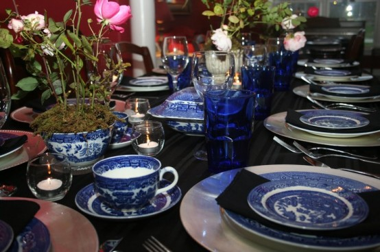 blue and white porcelain and blue glasses, a dark table and tender pink blooms plus candles create a chic tablescape