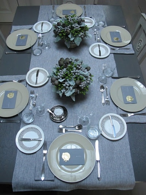 a stylish slate grey and blue Thanksgiving tablescape with a silver table runner, grey napkins and floral arrangements