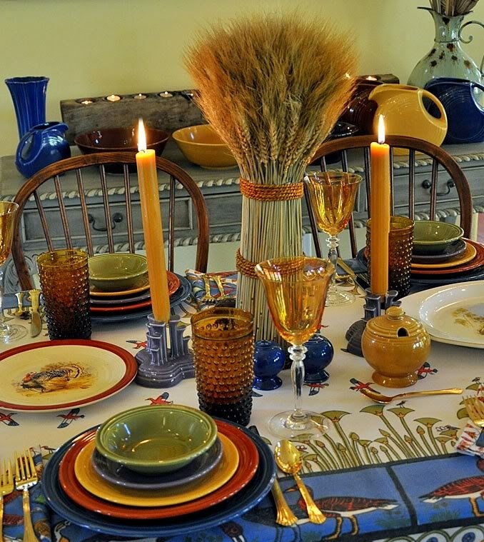a colroful fall table setting with bright porcelain, candles , wheat and blue porcelain candle holders and plates for a bolder look