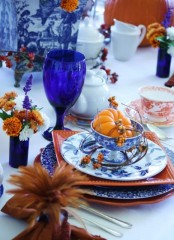 a bright and elegant Thanksgiving tablescape with orange and blue and white plates, bold blue glasses, blooms and berries
