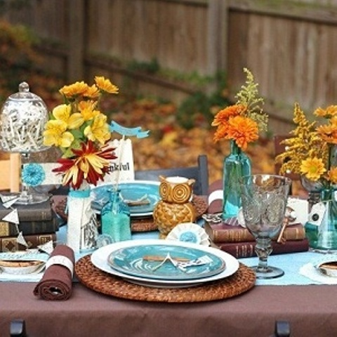 brown and turquoise table setting with bright blooms, woven placemats, owls and brown napkins
