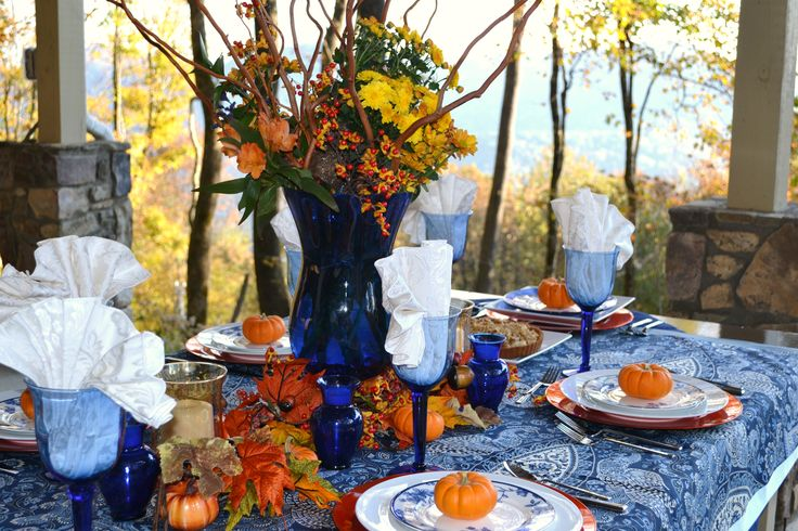 a blue printed tablecloth, bold blue glasses, candleholders and a vase make the tablescape chic, unusual and very bright