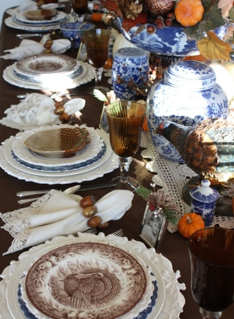 a traditional Thanksgiving tablescape done in brown, white, orange and spruced up with blue accents